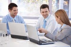 Équipe heureuse d'hommes d'affaires travaillant ensemble images stock