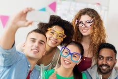 Équipe heureuse prenant le selfie à la fête au bureau Photo libre de droits
