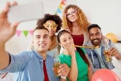 Équipe heureuse prenant le selfie à la fête au bureau Photographie stock