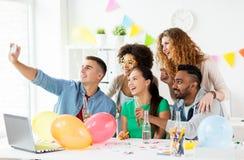 Équipe heureuse prenant le selfie à la fête au bureau Images libres de droits