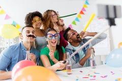 Équipe heureuse prenant le selfie à la fête au bureau Photographie stock libre de droits