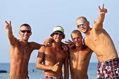Équipe joyeuse des amis ayant l'amusement à la plage Photos stock