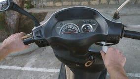 Équipe la main mettant en marche le moteur de scooter banque de vidéos