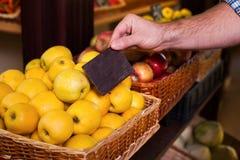 Équipe la main tient le prix à payer sur les pommes mûres Photo stock