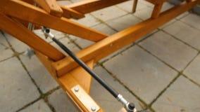 Équipe la main vérifiant le véhicule en bois de longévité avec l'hamac au lieu de la selle banque de vidéos