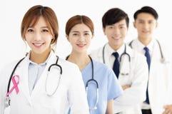 Équipe médicale avec le ruban rose de conscience de cancer du sein images stock