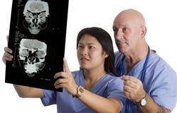 Équipe médicale contrôlant le rayon X de cerveau de patients Photographie stock libre de droits