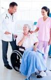 Équipe médicale de sourire prenant soin d'une femme aînée image libre de droits