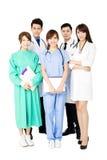 Équipe médicale de sourire se tenant ensemble d'isolement sur le blanc Photographie stock libre de droits