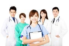 Équipe médicale de sourire se tenant ensemble d'isolement sur le blanc Photo stock