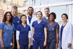 Équipe médicale de sourire se tenant ensemble en dehors d'un hôpital images stock