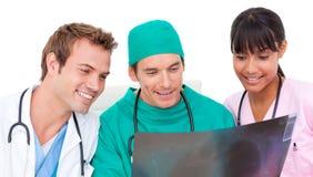 Équipe médicale enthousiaste regardant le rayon X Photos stock