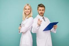 Équipe médicale heureuse des médecins, de l'homme indiquant la caméra et de la femme de sourire photo stock