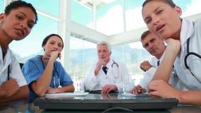 Équipe médicale regardant l'appareil-photo comme écran d'ordinateur banque de vidéos
