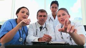 Équipe médicale travaillant ensemble sur un ordinateur clips vidéos