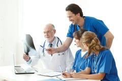 Équipe médicale vérifiant des résultats de rayon X Photos libres de droits