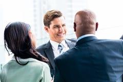 Équipe mélangée d'affaires discutant dehors Image stock