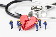 Équipe mignonne de travailleurs de technicienne de personnes miniatures avec la fixation uniforme d'aide ou réparer le coeur bris photos stock