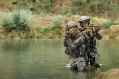 Équipe militaire traversant la rivière sous le feu Photos stock