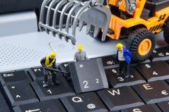 Équipe minuscule de jouets d'ingénieurs réparant l'ordinateur portable d'ordinateur de clavier C Photos libres de droits
