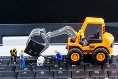 Équipe minuscule de jouets d'ingénieurs réparant l'ordinateur portable d'ordinateur de clavier C Images stock