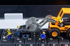 Équipe minuscule de jouets d'ingénieurs réparant l'ordinateur portable d'ordinateur de clavier C Image libre de droits