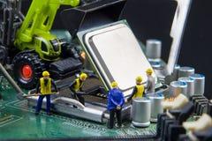 Équipe minuscule de jouets d'ingénieurs réparant le compu de carte mère de circuit Photographie stock libre de droits