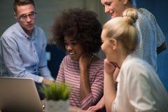 Équipe multi-ethnique de jeune entreprise dans le bureau de nuit image stock