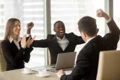 Équipe multi-ethnique heureuse d'affaires célébrant la victoire, soulevant l'ha photo stock