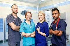 Équipe multiraciale de jeunes médecins dans un hôpital se tenant dans une salle d'opération Photographie stock