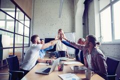 Équipe multiraciale réussie heureuse d'affaires donnant un geste de fives de haute comme elles rient et encouragent leur succès images stock