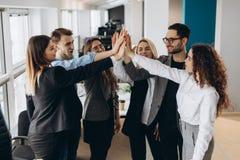 Équipe multiraciale réussie heureuse d'affaires donnant un geste de fives de haute comme elles rient et encouragent leur succès image libre de droits