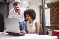 Équipe occasionnelle d'affaires regardant l'ordinateur portable ensemble image libre de droits