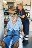 Équipe paramédicale soignant le patient sur la civière Images libres de droits