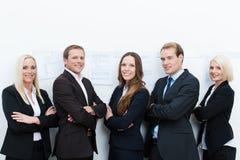 Équipe professionnelle heureuse se tenant avec les bras pliés Photos stock