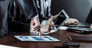 Équipe réussie d'affaires avec le comprimé numérique et diagrammes financiers pour le lieu de travail dans le bureau Photo stock