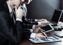 Équipe réussie d'affaires avec le comprimé numérique et diagrammes financiers pour le lieu de travail dans le bureau Image libre de droits