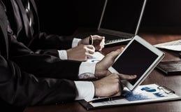 Équipe réussie d'affaires avec le comprimé numérique et diagrammes financiers pour le lieu de travail dans le bureau Images stock