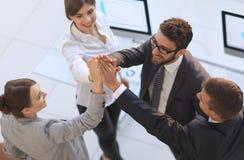 Équipe réussie d'affaires se donnant un top-là, se tenant dans le bureau Image libre de droits