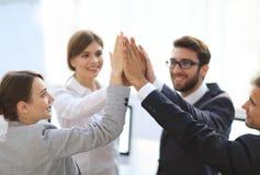 Équipe réussie d'affaires se donnant un top-là, se tenant dans le bureau Images libres de droits
