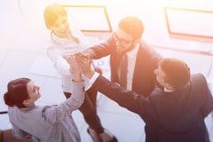 Équipe réussie d'affaires se donnant un top-là, se tenant dans le bureau Image stock
