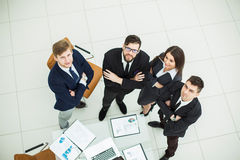équipe réussie d'affaires se tenant l'un à côté de l'autre près du lieu de travail dans le bureau Photo stock