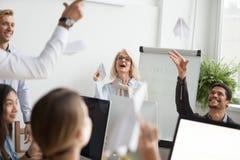 Équipe réussie d'employés divers heureux lançant l'avion de papier photo libre de droits