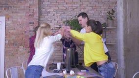 Équipe réussie, hommes d'affaires remontant leurs mains et soulever le leur au-dessus de la table dans le bureau moderne clips vidéos