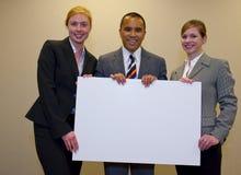 Équipe retenant un signe blanc Photo stock