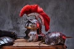 Équipement complet de combat du mensonge de guerrier du grec ancien sur une boîte de conseils en bois images stock