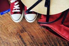 Équipement d'été des femmes s : espadrilles rouges, sac à dos, chapeau Substances de déplacement de fond et de touriste Vue supér Photographie stock libre de droits