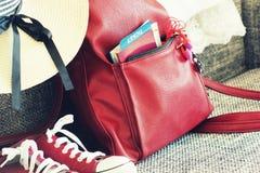 Équipement d'été des femmes s : espadrilles rouges, sac à dos, chapeau Substances de déplacement de fond et de touriste Vue supér Photographie stock