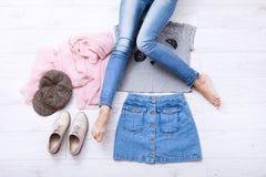 Équipement d'adolescent avec différents accessoires et jambes femelles dans des jeans sur le plancher en bois blanc L'espace de v Photos stock