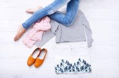 Équipement d'adolescent avec différents accessoires et jambes femelles dans des jeans sur le plancher en bois blanc L'espace de v Images stock